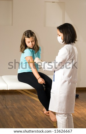 Female Doctor wearing a mask prepares the arm of a young girl who is sitting barefoot on an examining table. Both are watching intently. Vertically framed photograph - stock photo