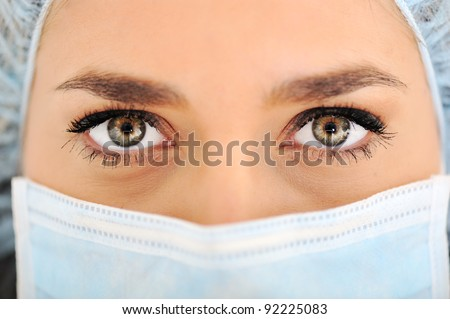 Female doctor wearing surgical cap and mask - stock photo