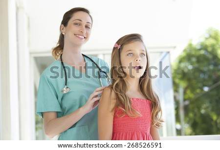 Female doctor with a young little girl patient - stock photo
