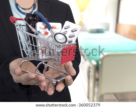 Female Doctor with black suit with hospital bed blur background. She's holding small shopping cart with colorful pills, syringe and stethoscope. Concept for health care costs or medical insurance. - stock photo
