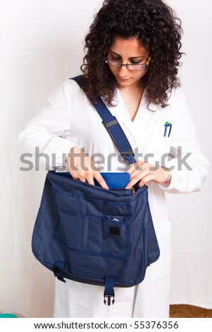 female doctor with clipboard  and bag - stock photo
