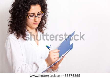 female doctor with clipboard her hands - stock photo