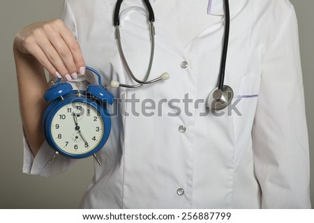 Female doctor with clock, standing on grey background