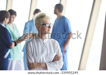 female doctor with glasses and blonde hairstyle  standing in front of team  in background, group of medical staff at hospital - stock photo