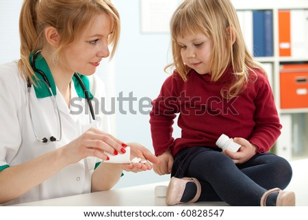female doctor with little girl in exam room - stock photo