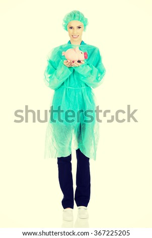 Female doctor with pink piggy bank. - stock photo