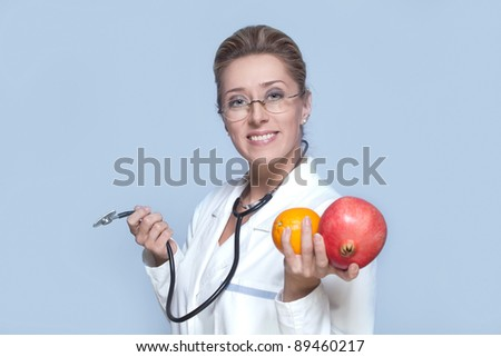 Female doctor with stethoscope and fruits smiling