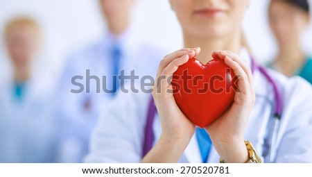 Female doctor with stethoscope holding heart . - stock photo