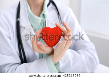 Female doctor with stethoscope holding heart.   Close up. - stock photo