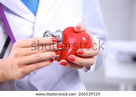 Female doctor with stethoscope holding heart, isolated on white background - stock photo