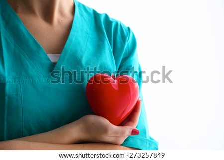 Female doctor with stethoscope holding heart over white background. - stock photo
