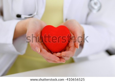 Female doctor with stethoscope holding heart.  Patients couple sitting in the background - stock photo