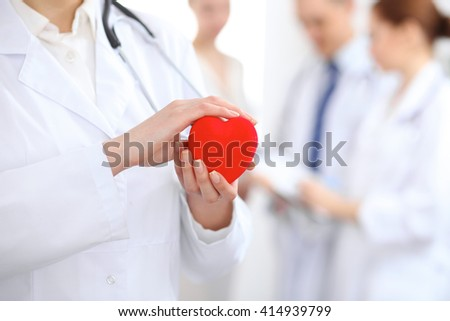 Female doctor with stethoscope holding heart.  Two doctors and patient  standing in the background - stock photo