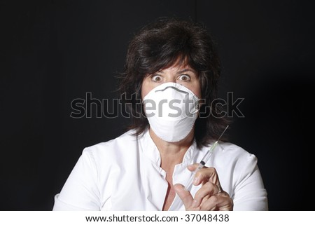 Female doctor with syringe and surgical mask  looking frightening - stock photo