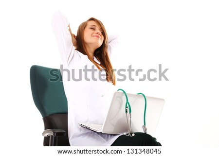 Female doctor working on her laptop stretching at her workplace against a white background - stock photo