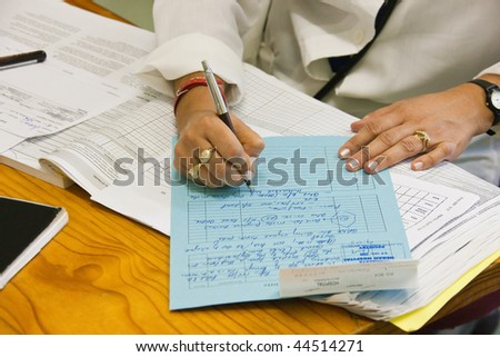 female doctor writing a file for a patient in the hospital - stock photo