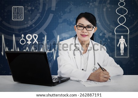 Female doctor writing a note with blue digital background - stock photo