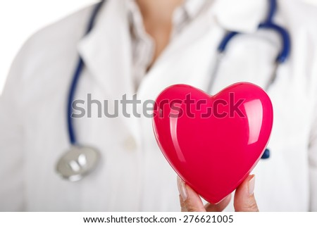 Female doctors's hand holding red toy heart. Doctor's hand closeup. Medical help or insurance concept. Cardiology care and health. - stock photo