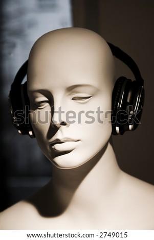Female doll with headphones - stock photo
