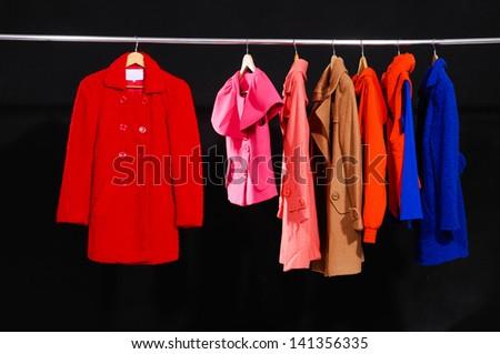 female dress, coat isolated on hanging-black background - stock photo