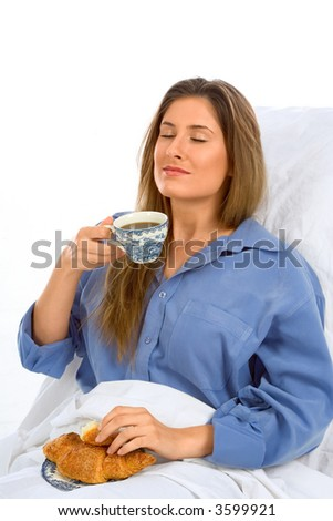 Female drinks her coffee with croissant in the bed