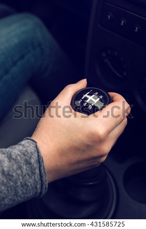 Female driver hand shifting gear manually, selective focus