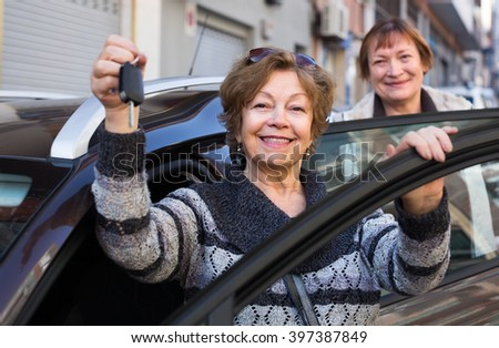 Female driver in golden age standing with new car key outdoor - stock photo