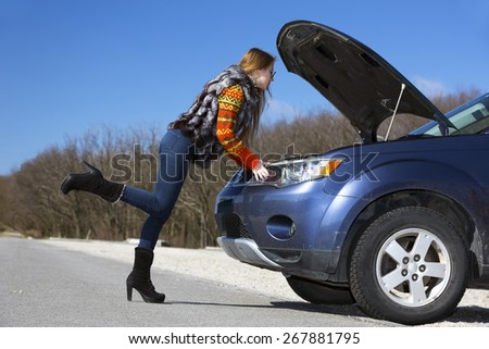 Female driver inspects her car engine. Elegant young woman looks under the engine hood of blue passenger car - stock photo
