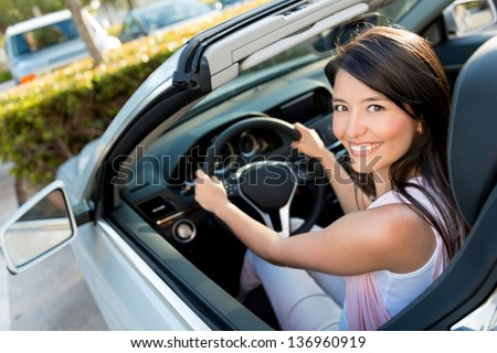 Female driver looking very happy driving a car