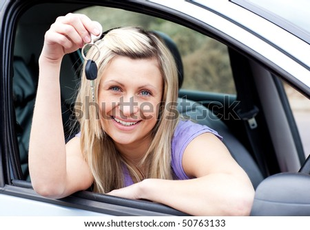 Female driver showing a key with a thumb up after buying a new car - stock photo