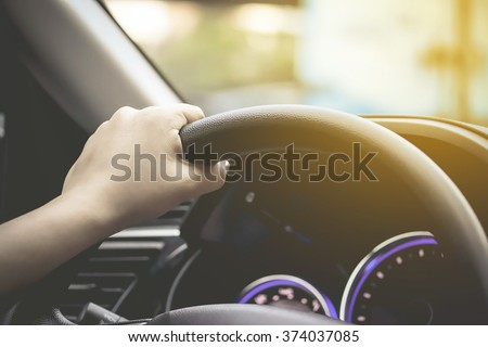 female driving car (left driver) - stock photo