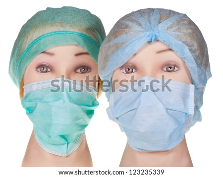 female dummy doctor heads wearing textile surgical cap and medical protective mask isolated on white background - stock photo