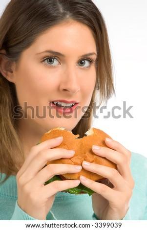Female eating fresh tasty hamburger with greenery - stock photo
