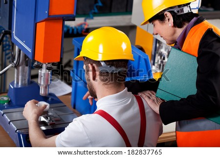 Female elder superior with young worker in warehouse - stock photo