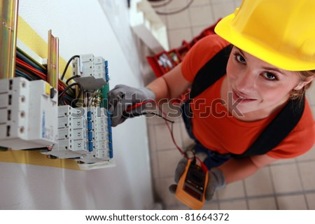 Female electrician checking fuse box