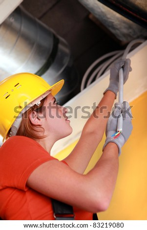 Female electrician pulling cables - stock photo