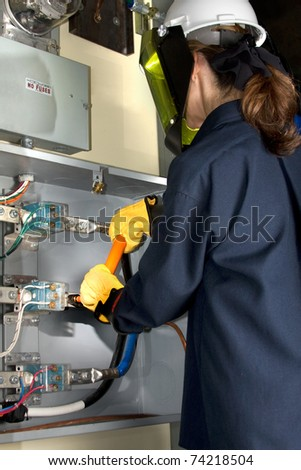 Female Electrician with protective clothing performing work in an energized panel. All trade marks removed or modified. - stock photo
