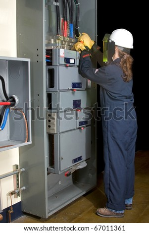 Female Electrician with protective clothing performing work in an energized panel, full body. All trade marks removed or modified - stock photo