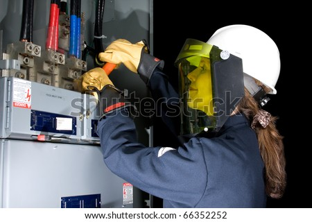 Female Electrician with protective clothing performing work in an energized panel with a happy smile. All trade marks removed or modified - stock photo