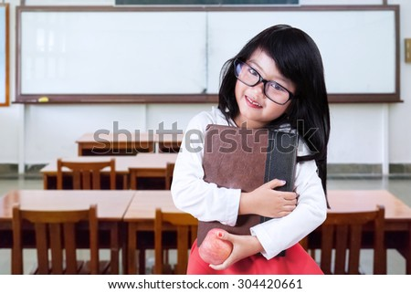Female elementary school student back to school and standing in the class while holding a book and apple - stock photo