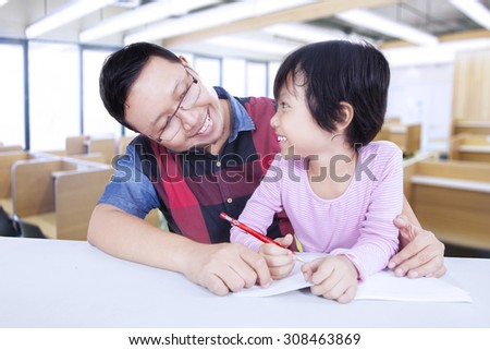 Female elementary school student studying in the classroom with male teacher and smiling to each other - stock photo