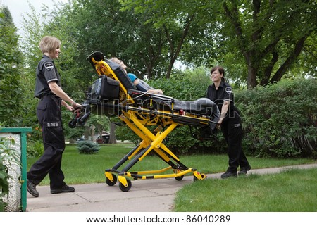 Female emergency medical team transporting senior patient on stretcher - stock photo