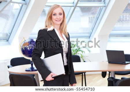 Female employee in her place of work and with her laptop in her hands - stock photo