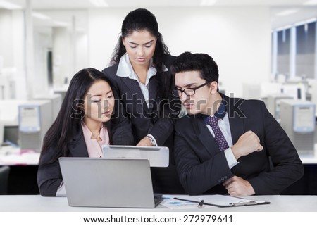 Female employee sharing business information on the tablet with her partners in the office