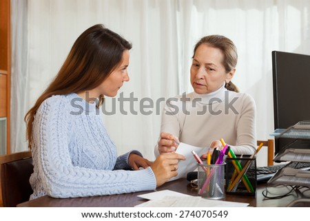 Female employee talking with young woman at office