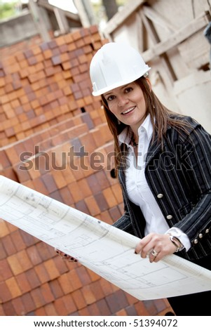 Female engineer at a construction site holding blueprints - stock photo