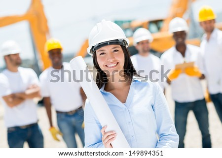 Female engineer at a construction site looking happy  - stock photo