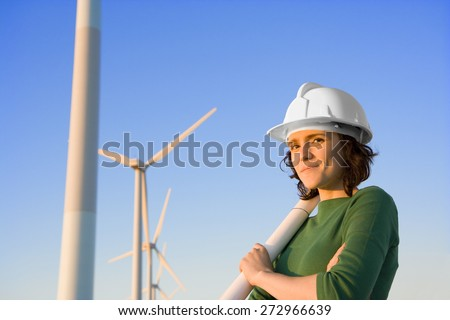 Female Engineer Holding Blueprints in Front of Modern Wind Turbines - stock photo