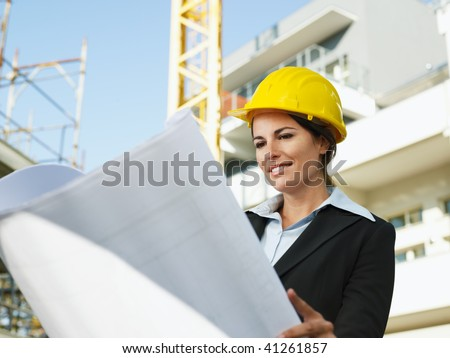 female engineer looking at blueprints in construction site - stock photo