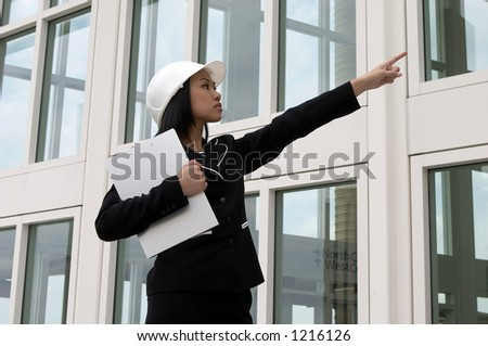 Female Engineer Pointing at Construction - stock photo